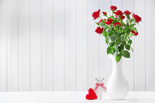Bouquet Of Red Roses In Vase On Wooden Planks Background