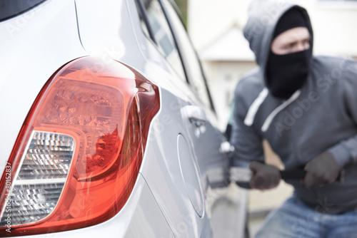 Fotografía  Masked Man Breaking Into Car With Crowbar