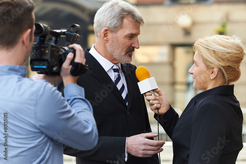 Fényképezés  Female Journalist With Microphone Interviewing Businessman