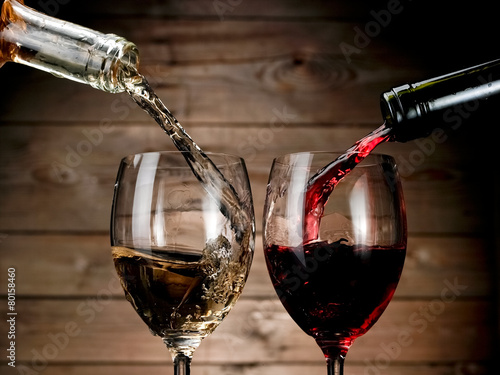 Fotografiet  Red and white wine pouring on wood background