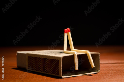 Fotografie, Obraz  Two match humans sitting on matchbox on a dark background
