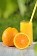 szklanka smacznego soku pomarańczowego i pomarańcze na stole