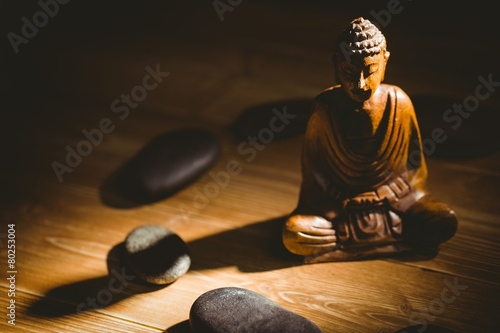 Stampa su Tela Wooden buddha statue on table
