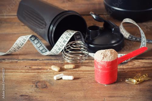 Fotografia  Białko serwatki w proszku w szufelce z witaminami i wytrząsarką z tworzywa sztuc