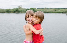 Fraternal Twins Hugging At The Beach