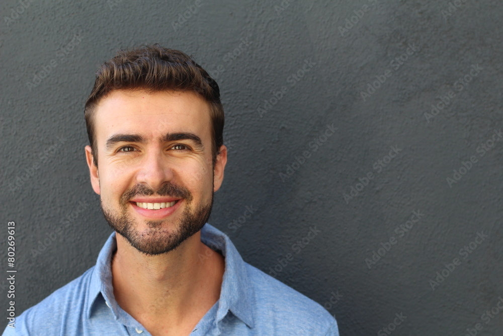 Fototapeta Portrait of a happy young man smiling on gray background