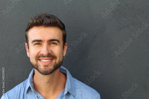 Fototapeta Portrait of a happy young man smiling on gray background obraz