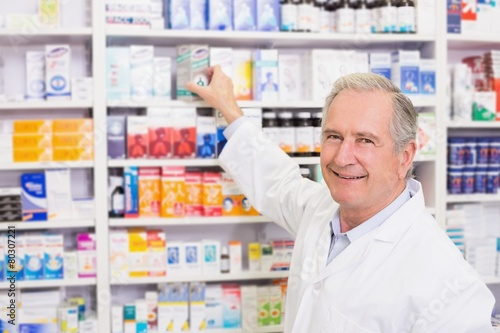 Staande foto Apotheek Smiling pharmacist taking medicine from shelf