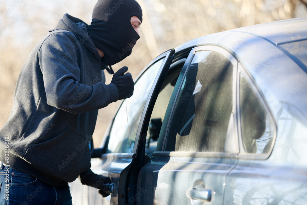 Fototapeta Thief stealing automobile car at daylight street in city