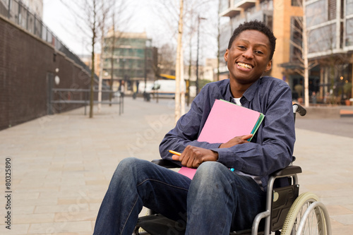 Photo  happy young disabled man in a wheelchair holding folders.