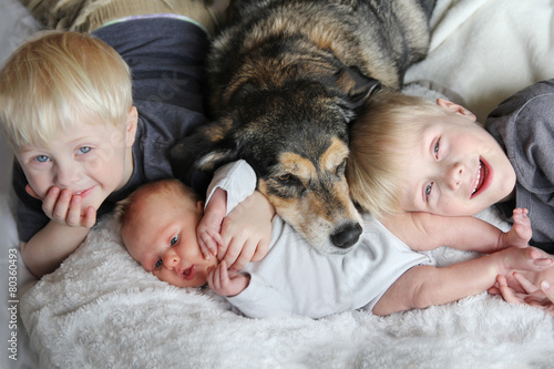 Photo  Three Happy Young Children Snuggling with Pet Dog in Bed