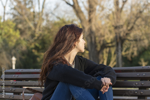 Fotomural Pensive beautiful woman in the park looking away.