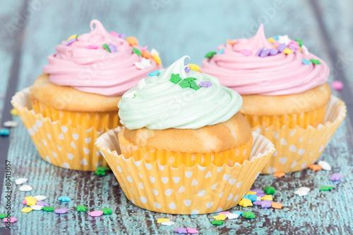 Fotografie, Obraz  Pastel cupcakes with sprinkles on blue vintage background