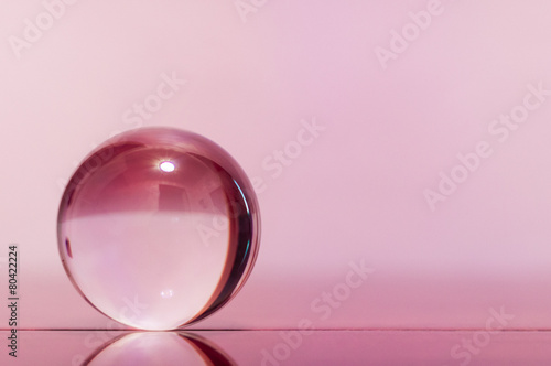 Fotografia Glass transparent ball on light pink background and mirror