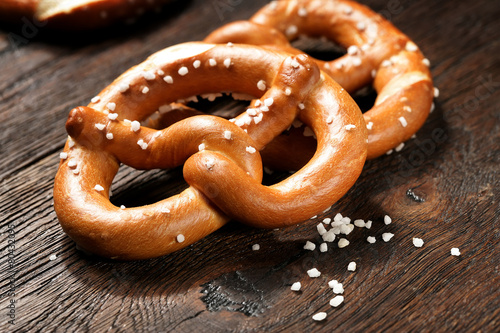 Cuadros en Lienzo Fresh pretzels with sea salt close-up on  dark board background