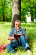 old man reading a book in the forest