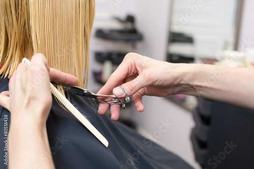A hairdresser making a haircut for a blonde girl