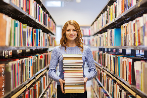 happy student girl or woman with books in library Fototapeta