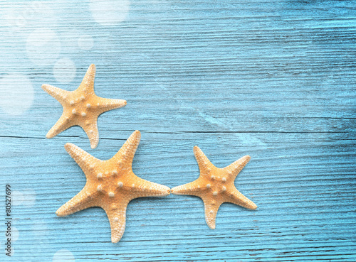 Three starfish on a blue wooden background Wallpaper Mural