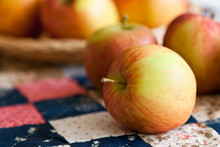 Fresh Apples On A Vintage Quilt Of Small Squares. Close Up