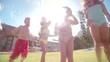 Mixed racial group of kids throwing water balloons at camera