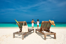 Couple In White Running On A Beach At Maldives