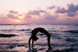 Young woman practicing gymnastic bridge on the beach at sunset