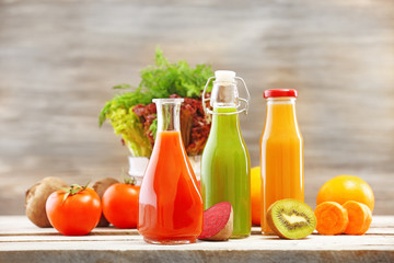 Fototapeta samoprzylepna Glass bottles of fresh healthy juice with set of fruits and