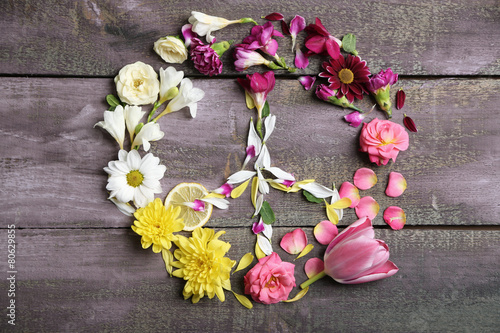 Peace symbol of beautiful flowers, on wooden table Poster