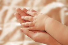 Children's Hand Lies On A Hand Mother