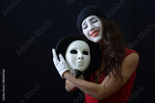 Photo  the girl is MIME holding a white mask and smiles