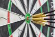 Dart board with darts on bullseye