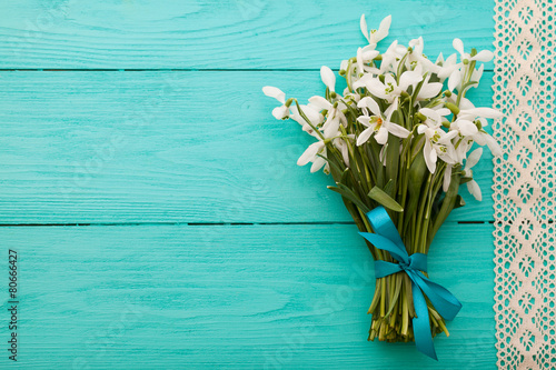 Flowers and lace ribbon on blue wooden background