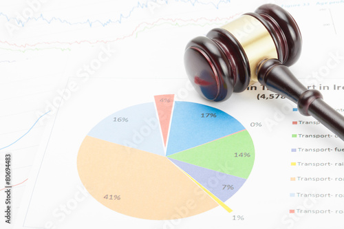 Foto Wooden judge's gavel over colorful diagram