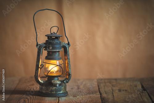 vintage kerosene oil lantern lamp burning with a soft glow light Wallpaper Mural
