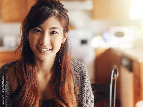 Fotografia  happy smiling asian teen girl portrait in kitchen