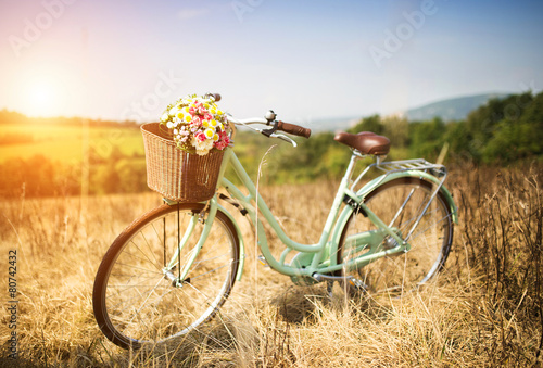 Ingelijste posters Fiets Vintage bicycle with basket full of flowers standing in field