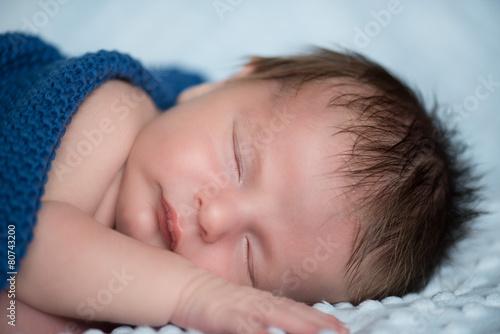 Fototapeta Śpiący noworodek pod niebieskim kocykiem. obraz
