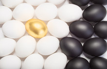 Gold Easter Egg Between Many White And Black Eggs