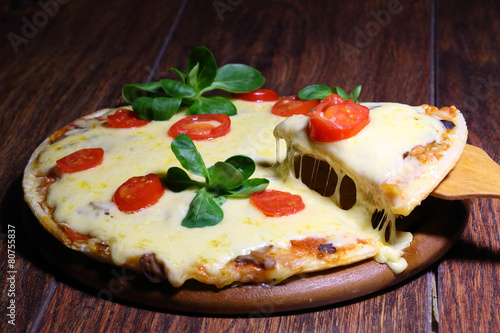Wall Murals Pizzeria Piece of a pizza with the fused cheese on a wooden shovel
