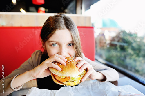 Fotobehang Kruidenierswinkel Cute little girl eating a hamburger