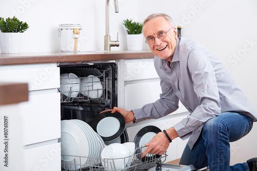 Foto  Älterer Mann in der Küche, entleeren Sie den Geschirrspüler 4