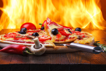FototapetaPizza on wooden table with real oven fire on backgroud