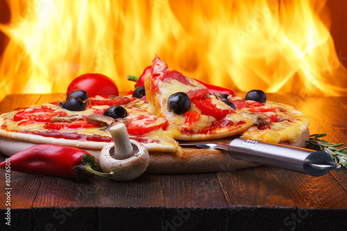 Pizza on wooden table with real oven fire on backgroud - 80765011