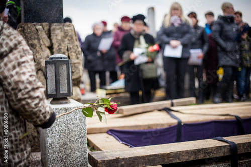 Photo  Group of mourners staying by the opened grave at a cemetery