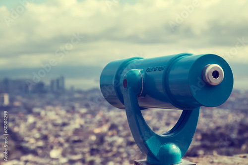 Fotografiet  Blue telescope and blurred city on background.