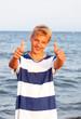 Teenager mit Daumen hoch am Meer