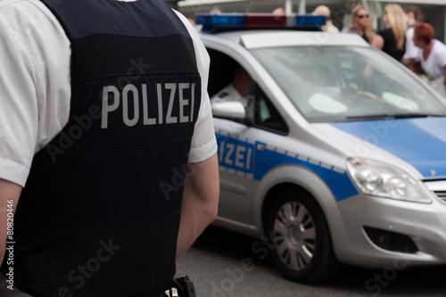 Fotografía  Polizist und Streifenwagen vor einer Menschenmenge