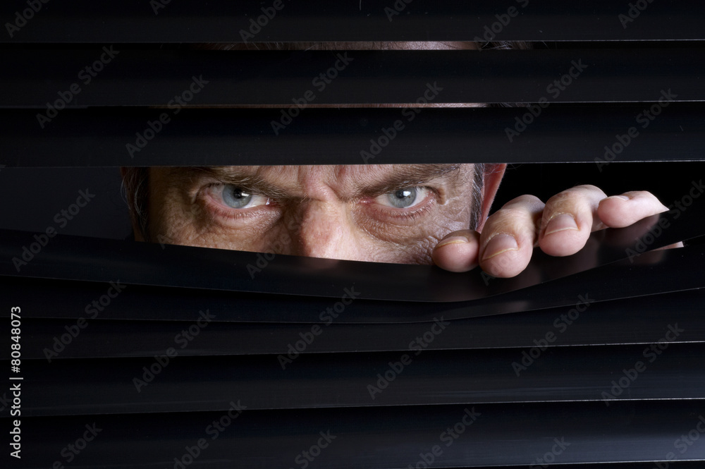Fototapeta Man spying on something through venetian blinds