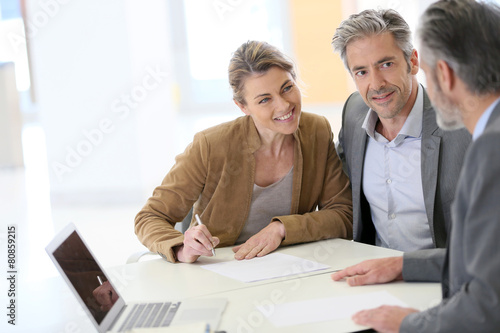 Fotografie, Obraz  Mature couple signing financial contract at the bank